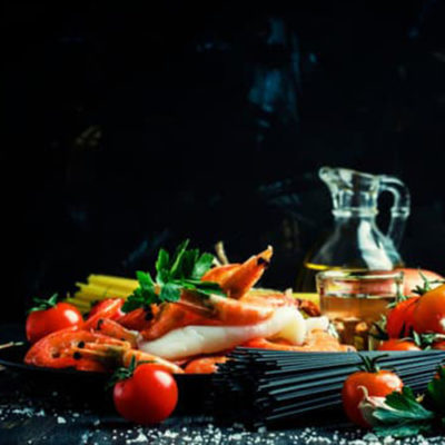 Ingredients for the preparation black pasta with seafood, tomatoes and wine, black background, selective focus