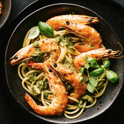 Tasty spaghetti pasta mit prawns and sauce pesto on dark table background. Served and ready to eat. Horizontal with copy space.